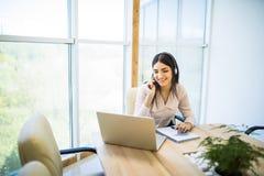 Jeune femme avec du charme heureuse s'asseyant et travaillant avec l'ordinateur portable utilisant le casque dans le bureau image libre de droits