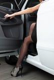 Jeune femme avec du charme s'asseyant dans une voiture Photo libre de droits