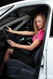 Jeune femme avec du charme s'asseyant dans une voiture Photographie stock libre de droits