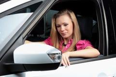 Jeune femme avec du charme s'asseyant dans une voiture Photos libres de droits