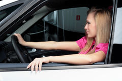 Jeune femme avec du charme s'asseyant dans une voiture Photos stock
