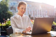 Jeune femme avec du charme travaillant sur l'ordinateur portable en café Photos libres de droits
