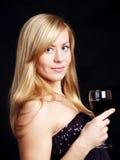 Jeune femme avec du vin au-dessus de l'obscurité Image libre de droits