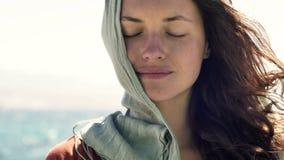 Jeune femme avec l'écharpe sur la tête et les yeux fermés se tenant en vent contre un paysage de mer banque de vidéos