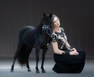 Jeune femme avec l'étalon noir Cheval miniature américain Images stock