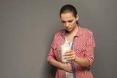 Jeune femme avec l'allergie de laiterie tenant le verre de lait photos libres de droits