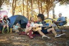 Jeune femme avec l'ami masculin jouant la guitare au terrain de camping Photographie stock