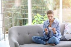 Jeune femme avec l'essai de grossesse à la maison image stock