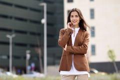Jeune femme avec l'extérieur debout de cheveux intéressants de l'immeuble de bureaux Image libre de droits