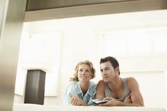 Jeune femme avec l'homme jugeant à télécommande Photographie stock libre de droits