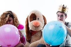 Jeune femme avec l'homme soufflant de grands ballons Images stock
