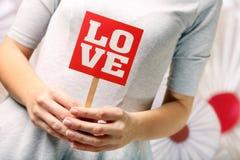 Jeune femme avec l'inscription d'amour le jour de valentines Images stock