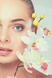 Jeune femme avec l'orchidée, sur le fond blanc Photographie stock