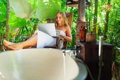 Jeune femme avec l'ordinateur portable dans la salle de bains extérieure tropicale Images libres de droits