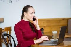 Jeune femme avec l'ordinateur portable en café parlant au téléphone portable Photographie stock libre de droits