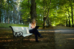 Jeune femme avec l'ordinateur portable en parc photo stock