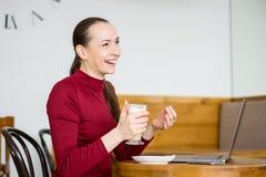Jeune femme avec l'ordinateur portable et le téléphone portable en café Photographie stock libre de droits