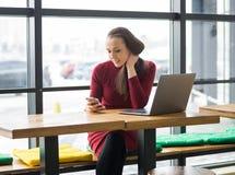 Jeune femme avec l'ordinateur portable et le téléphone portable en café Image stock