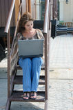 Jeune femme avec l'ordinateur portable sur les étapes du vieux train Image libre de droits