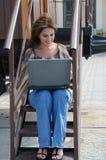 Jeune femme avec l'ordinateur portable sur les étapes du vieux train Images stock