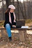 Jeune femme avec l'ordinateur portatif à l'extérieur photos libres de droits