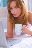 Jeune femme avec l'ordinateur portatif Photographie stock libre de droits