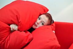 Jeune femme avec l'oreiller rouge Photo stock