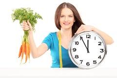 Jeune femme avec la bande de mesure tenant des carottes et une horloge murale Image libre de droits