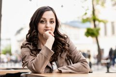 Jeune femme avec la jeune belle femme blanche de longs cheveux bruns avec les cheveux bruns bouclés à une table dans la perspecti images stock