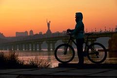 Jeune femme avec la bicyclette contre le ciel au coucher du soleil Images libres de droits