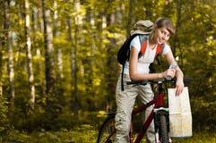 Jeune femme avec la bicyclette dans la forêt photos stock