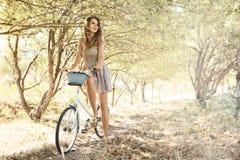 Jeune femme avec la bicyclette en stationnement Images libres de droits