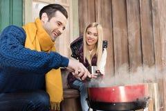 Jeune femme avec la boisson chaude regardant l'homme heureux grillant la viande sur le porche Images libres de droits