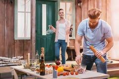 Jeune femme avec la bouteille et les verres de vin regardant l'homme préparant la viande pour le BBQ Photo libre de droits