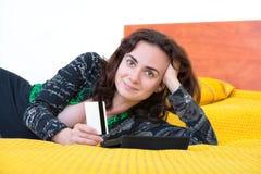 Jeune femme avec la carte de crédit et le comprimé Image libre de droits