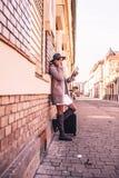 Jeune femme avec la carte et valise dans la rue de ville Photos stock