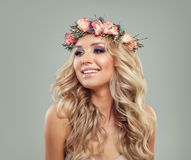 Jeune femme avec la coiffure de fleurs et bouclé heureux image stock