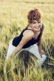 Jeune femme avec la coiffure exagérée dans le domaine de blé Photos stock