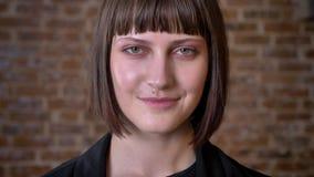 Jeune femme avec la coupe de cheveux courte et les yeux verts regardant l'appareil-photo et souriant, d'isolement sur le fond de  banque de vidéos