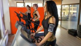 Jeune femme avec la courroie de bras de traqueur de smartphone s'exerçant dans le gymnase de forme physique banque de vidéos