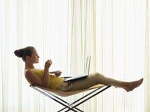 Jeune femme avec la cuvette de café utilisant l'ordinateur portatif à la maison Photo stock