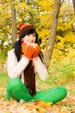 Jeune femme avec la cuvette de thé en stationnement d'automne Photographie stock libre de droits