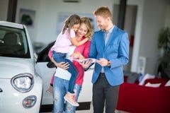 Jeune femme avec la fille parlant avec le concessionnaire automobile Images libres de droits