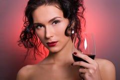 Jeune femme avec la glace de vin rouge image stock
