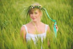 Jeune femme avec la guirlande sur sa tête dans un domaine de blé Images libres de droits