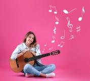 Jeune femme avec la guitare acoustique sur le fond de couleur images stock