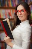 Jeune femme avec la lecture en verre Image stock