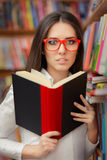 Jeune femme avec la lecture en verre Images stock