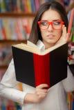 Jeune femme avec la lecture en verre Photographie stock libre de droits