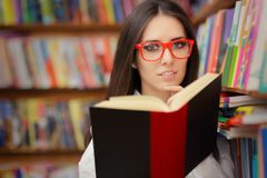 Jeune femme avec la lecture en verre Photo stock